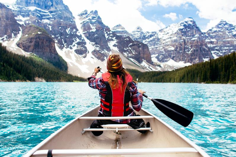 Woman canoeing through a beautiful mountainous region