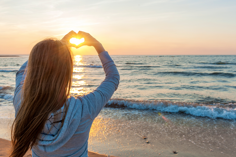 Woman with long hair making a heart with her hands around the sunset