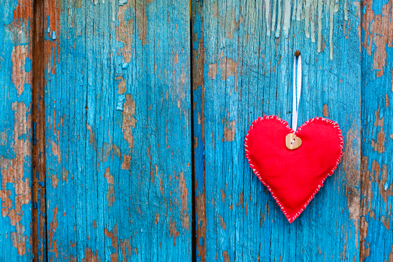 Red felt heart ornament hanging on a wooden fence with peeling blue paint