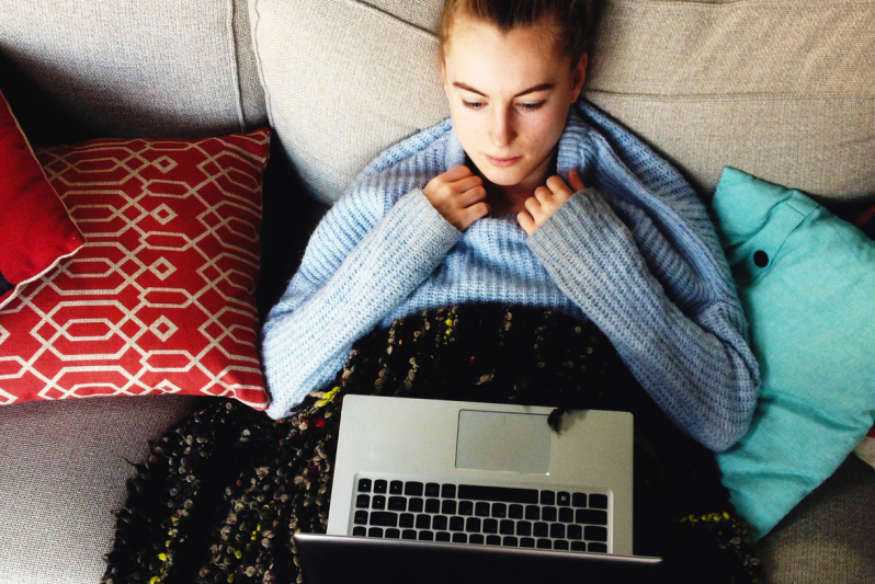 Young woman lying on a couch looking at her laptop