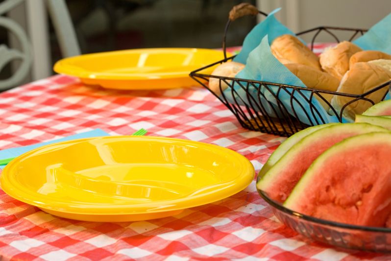 Picnic table with plastic plates and watermelon