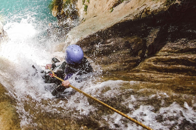 Person rapelling down a waterfall
