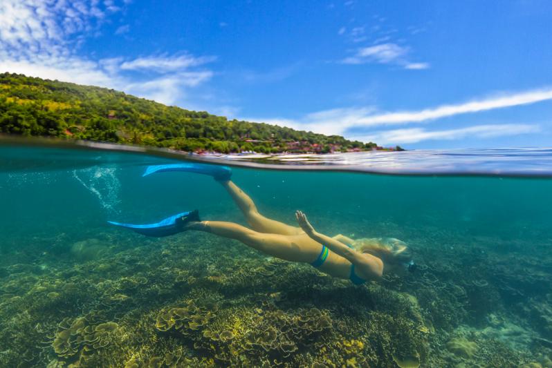 Woman snorkeling among coral
